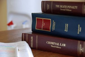 A stack of law books covering law practices held at the Law Offices of Jerod Gunsberg in Los Angeles, CA