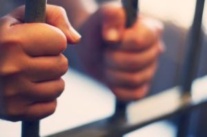 Hands behind bars representing the criminal law services from the Law Offices of Jerod Gunsberg in Los Angeles, CA