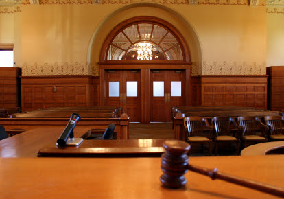 A view of a courtroom from the judge's stand with a gavel resting on the stand representing legal defense by the Law Offices of Jerod Gunsberg in Los Angeles, CA